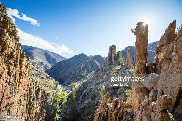 one young woman climber stretches toward the pinnacle's peak high above canyon, surrounded by sky - pinnacle peak stock pictures, royalty-free photos & images