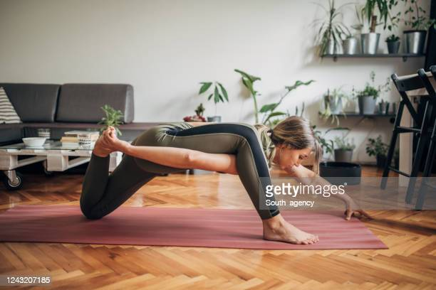 one young woman doing yoga on exercise mat at home - active lifestyle stock pictures, royalty-free photos & images