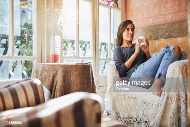 eine junge frau, eine tasse kaffee zu hause trinken. - hygge stock-fotos und bilder