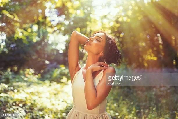 Eine junge Frau sich kostenfrei im Freien im sonnigen Park