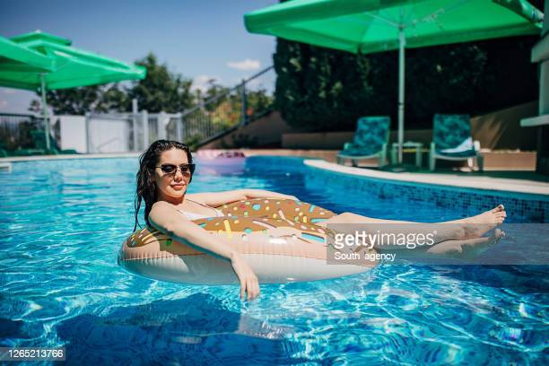 one young woman floating on the rubber ring as a donut in the swimming pool - escaping stock pictures, royalty-free photos & images