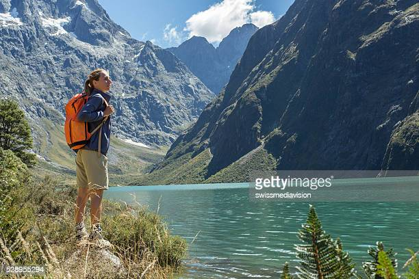 one young woman hiking, reaches mountain lake - southland new zealand stock pictures, royalty-free photos & images
