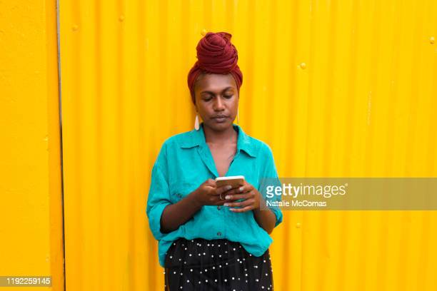 one young woman in front of a yellow wall - showus stock pictures, royalty-free photos & images