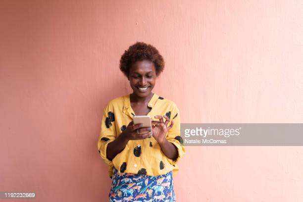 one young woman in front of pink wall smiling on mobile phone - showus foto e immagini stock