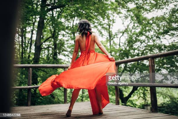 one young woman in red dress dancing alone in nature - red dress stock pictures, royalty-free photos & images