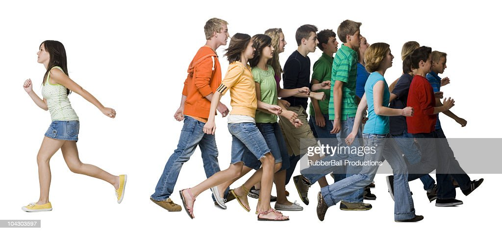 one young woman standing apart from a group of teenagers : Stock Photo