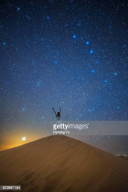 One young woman standing on top of sand dune with arms up with starry sky background. Composite image.