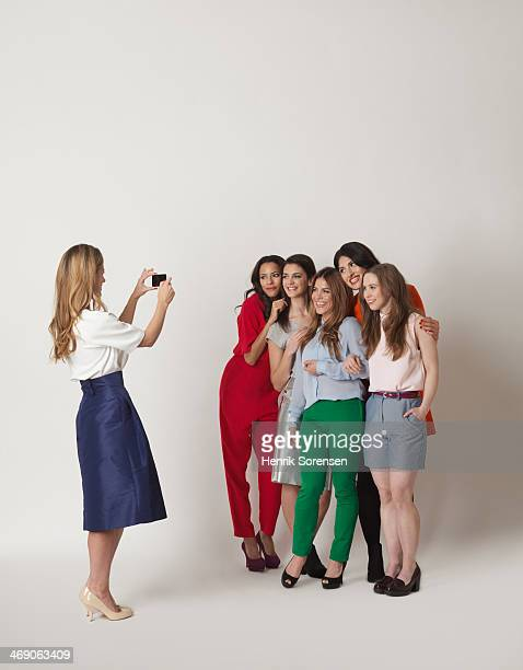 One young woman taking five young women's picture