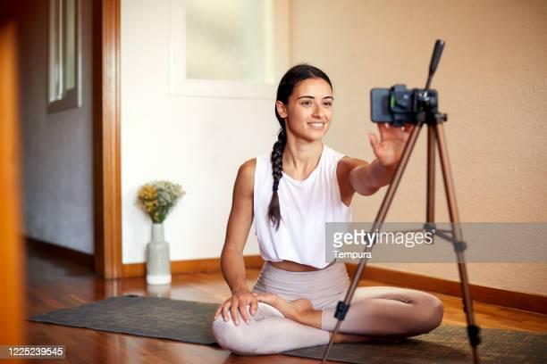 una joven enseña yoga en línea desde casa. - influencer fotografías e imágenes de stock