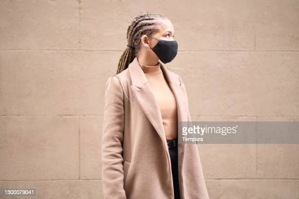 one young woman wearing a coat and a protective face mask. - one young woman only stock pictures, royalty-free photos & images