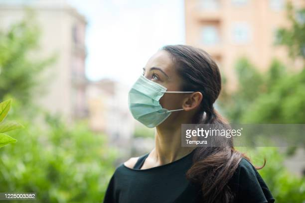 one young woman wearing a surgical mask outdoor - ease stock pictures, royalty-free photos & images