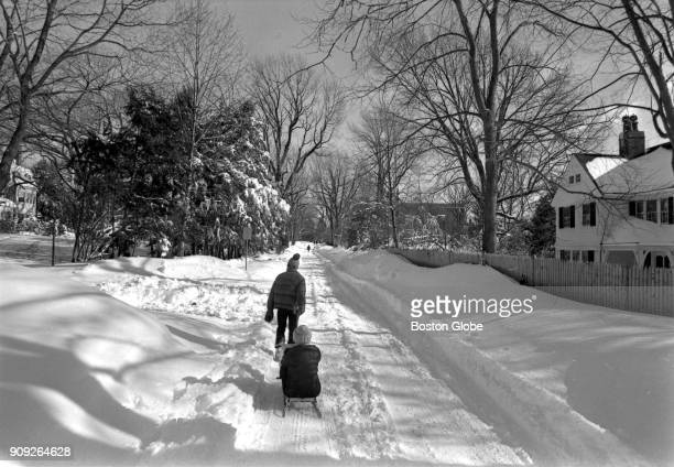 One youngster pulls another on a sled along a snowcovered road in Newton MA following the Blizzard of 78 on Feb 9 1978