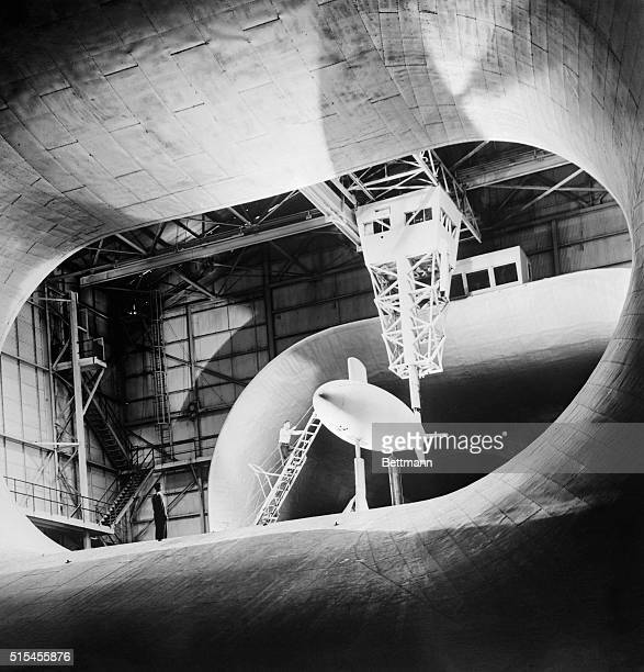 A onefifth scale model of the Albacore believed to be the world's fastest submarine is approached by a technician during wind tunnel tests at Langley...