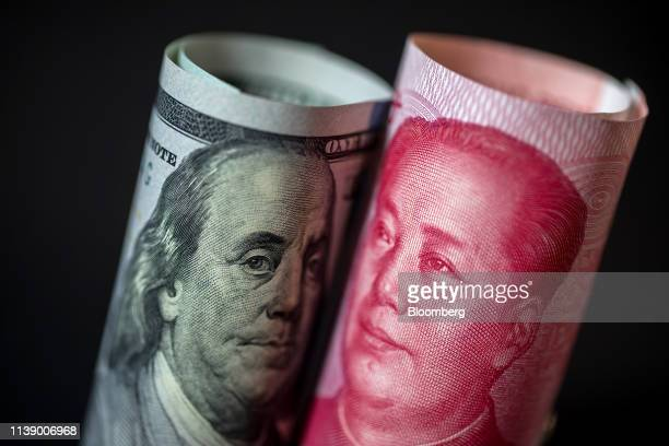 A US onehundred dollar banknote and a Chinese onehundred yuan banknote are arranged for a photograph in Hong Kong China on Monday April 15 2019...