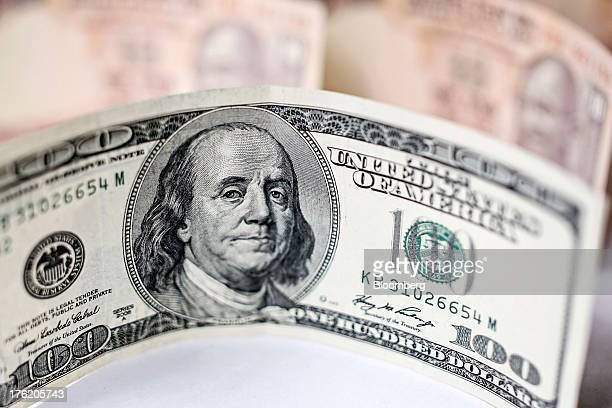 A US onehundred dollar banknote and Indian 10 rupee banknotes are arranged for a photograph in Mumbai India on Saturday Aug 10 2013 India plans to...