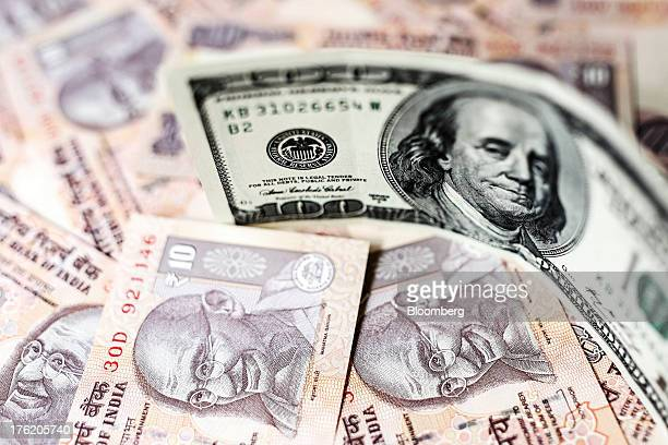 A US onehundred dollar banknote and Indian ten rupee banknotes are arranged for a photograph in Mumbai India on Saturday Aug 10 2013 India plans to...