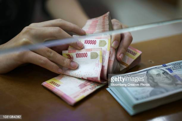 U.S. one-hundred dollar banknotes and Indonesian 100,000 rupiah banknotes