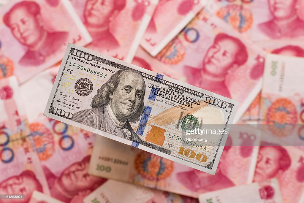 A U.S. one-hundred dollar bill sits on a pile of Chinese one-hundred yuan banknotes in this arranged photograph taken in Hong Kong, China, on Monday, July 20, 2015. The yuan has proven to be among the more resilient emerging-market currencies this year, having fallen less than 0.1 percent versus the dollar as China cut interest rates and the U.S. prepared to raise. Photographer: Xaume Olleros/Bloomberg via Getty Images