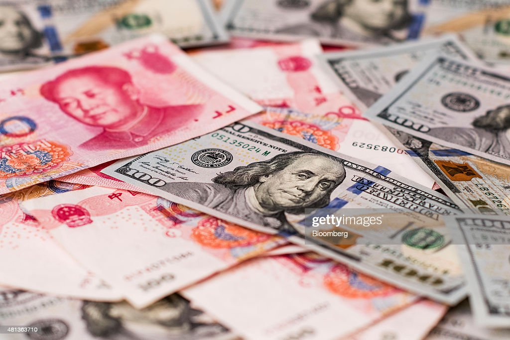 U.S. one-hundred dollar bills and Chinese one-hundred yuan banknotes are arranged for a photograph in Hong Kong, China, on Monday, July 20, 2015. The yuan has proven to be among the more resilient emerging-market currencies this year, having fallen less than 0.1 percent versus the dollar as China cut interest rates and the U.S. prepared to raise. Photographer: Xaume Olleros/Bloomberg via Getty Images