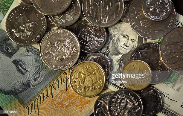 A onehundreddollar note and coins from Australia are displayed against an American onedollar bill in Sydney Australia on Tuesday July 24 2007 The...