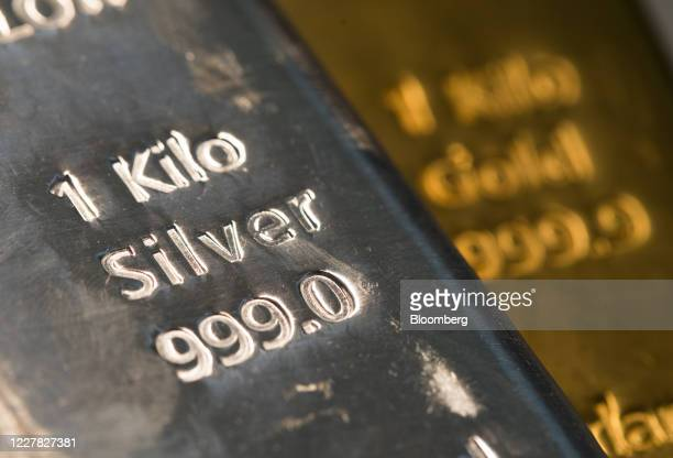 One-kilogram silver bar, left, sits on top of a one-kilogram gold bar at Gold Investments Ltd. Bullion dealers in this arranged photograph in London,...