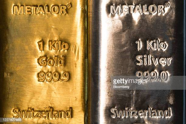 One-kilogram silver bar, right, sits next to a one-kilogram gold bar at Gold Investments Ltd. Bullion dealers in this arranged photograph in London,...