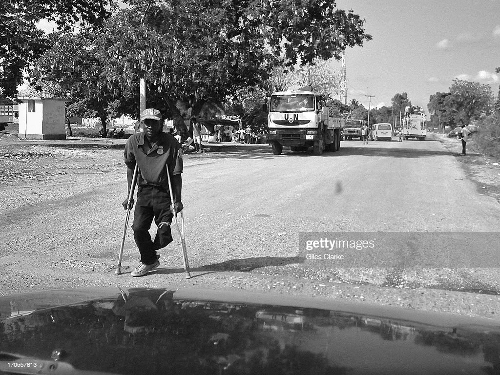 A one-legged man hobbles along a ruined street March 20, 2013 in Leogane, Haiti. This town, 20 miles to the west of Port-au-Prince, was the epicenter of 7.0 earthquake in 2010. Over 90% of the town's infrastructure was destroyed and officials estimate that some 25,000 inhabitants died that day.