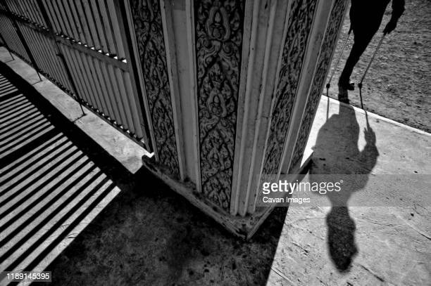 one-legged man with crutch entering the museum of genocide tuol sleng - torture stock pictures, royalty-free photos & images