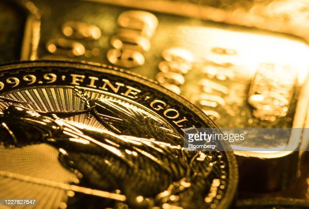 One-ounce Britannia gold coin sits on one hundred gram gold bars at Gold Investments Ltd. Bullion dealers in this arranged photograph in London,...