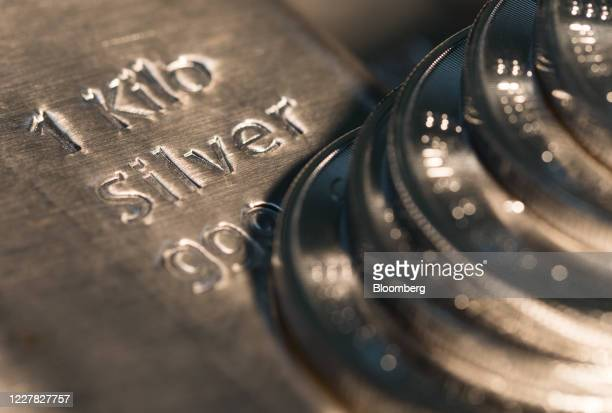 One-ounce silver coins sit on a one-kilogram silver bar at Gold Investments Ltd. Bullion dealers in this arranged photograph in London, U.K., on...