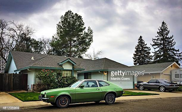 Onestory house with an old used Ford Pinto sitting in front of it California