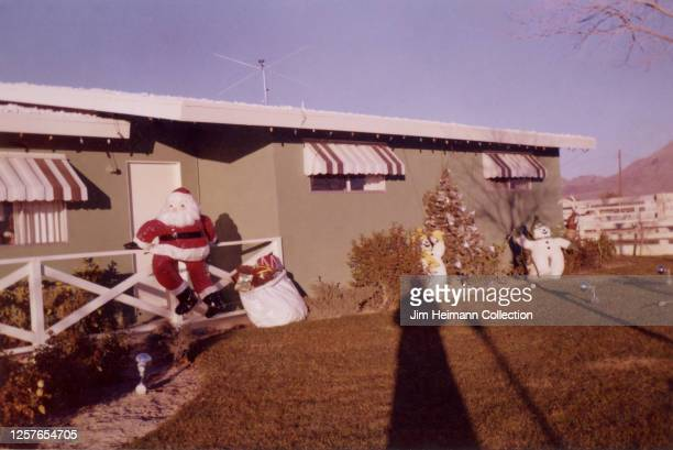 A onestory residential house in California is decorated with Christmas ornaments including a lifesize Santa Claus model that is seen hopping over a...