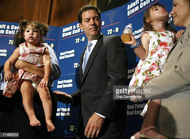 One-year-old Abby Pell, held by her mother Cathy Pell, and Elisha Lancaster held by her mother Maria Lancaster, join Sen. Sam Brownback for news...