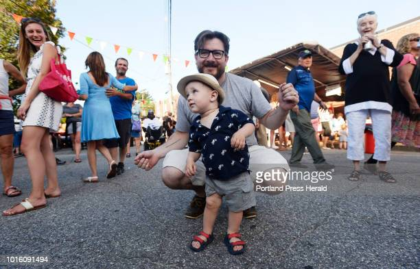 Oneyearold Carter dances to the music of of The Carmine Band along with his father Chris Sullivan during the St Peter's Church Italian Bazaar in...