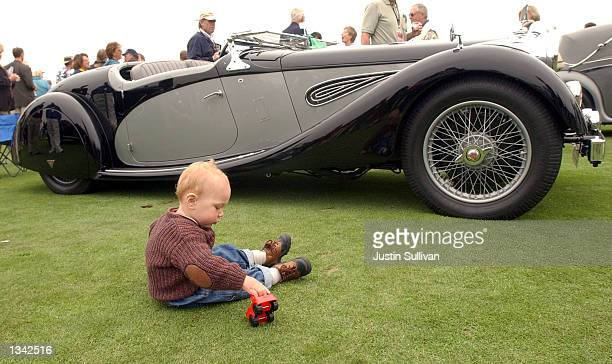 Oneyearold Gavin Hart plays with a toy car in front of a 1937 Alvis on display at the 2002 Pebble Beach Concours d'Elegance August 18 2002 in Pebble...