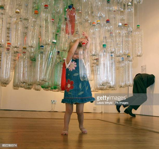 Oneyearold Phoebe Cordy walks through Black Cube created by artist Nick Ball from 663 twolitre plastic bottles at the Bankside Gallery in central...