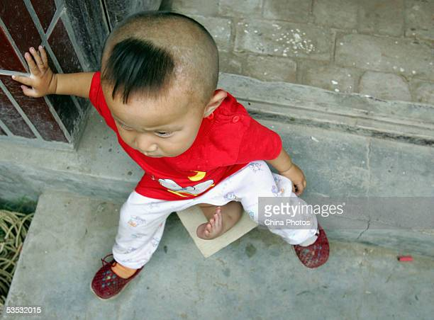 Oneyearold Wei Wei a young child with three legs and both female male reproductive organs plays at the Dongzhimen Hospital on August 29 2005 in...