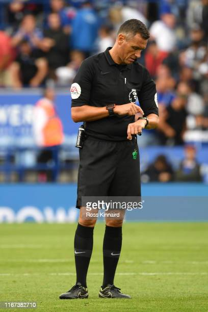 Onfield referee Andre Marriner looks at his watch at fulltime after the Premier League match between Leicester City and Wolverhampton Wanderers at...