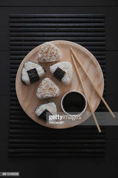 onigiris, bowl with soy sauce and chopsticks on wooden plate - rice ball stock pictures, royalty-free photos & images