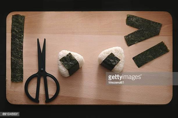Onigiris, strips of nori and scissors on chopping board
