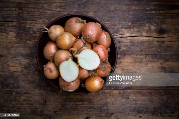onions in a wooden bowl on dark wood