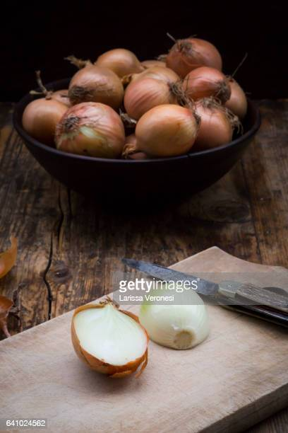 onions on dark wood, cutting board and knife