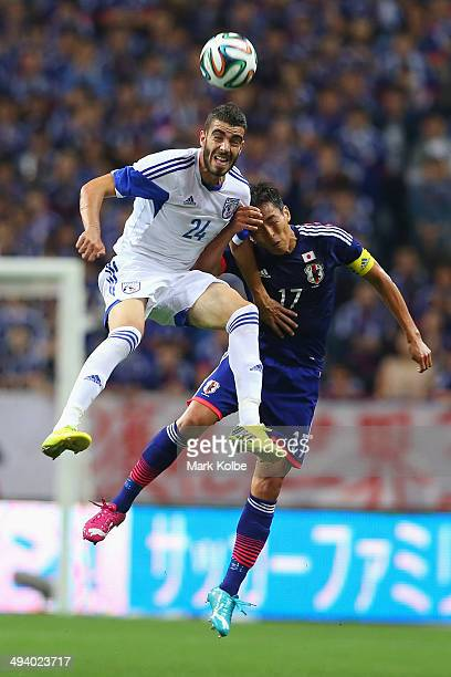 Onisiforos Roushias of Cyprus and Makoto Hasebe of Japan compete for the ball in the air during the Kirin Challenge Cup international friendly match...