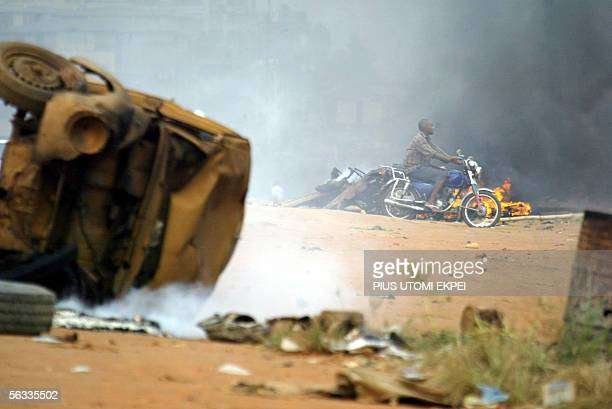 Motocyclist passes by a bonfire and a vehicle set ablaze by the banned Movement for the Actualisation of a Sovereign State of Biafra in Onitsha, 05...