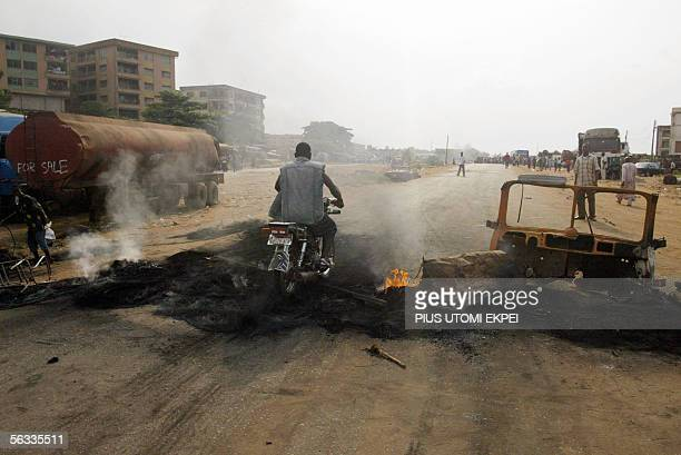 Motocyclist tries passes by a bonfire set by the banned Movement for the Actualisation of a Sovereign State of Biafra in Onitsha, 05 December 2005....