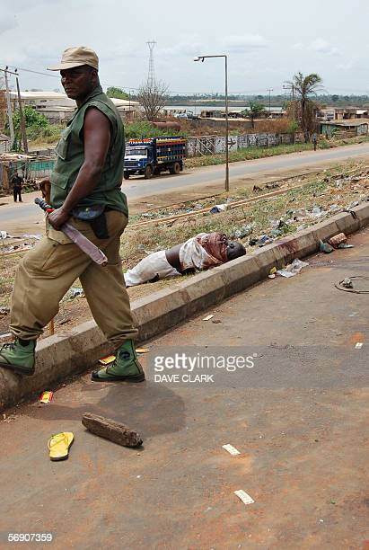 A Nigerian policeman stands 22 February 2006 beside the body of a murdered Muslim victim to a lynchmob in the southern Nigerian city of Onitsha...