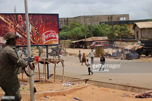 A Nigerian policeman threatens a Christian lynch mob with an assult weapon 22 February in the southern Nigerian city of Onitsha as the body of one of...