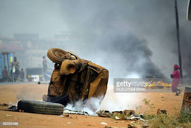 Woman tries to run past a bonfire and a vehicle set ablaze by the banned Movement for the Actualisation of a Sovereign State of Biafra in Onitsha, 05...