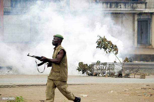 An anti-riot police officer leaves the scene with billowing smoke from police teargas shot to disperse members of the banned Movement for the...