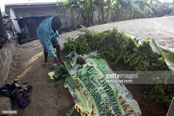 Martin Uzoma tries to cover the face of his relation Ikechukwu Okere allegedly shot by antiriot police at Ogbefere road 06 December 2005 while...